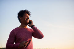 Happy man talking on mobile phone. Outdoors. Low angle on sky background stock photo
