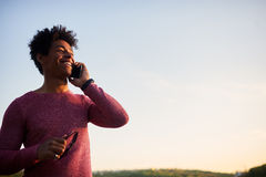 Happy man talking on mobile phone. Happy man talking on phone outdoors. Low angle on sky background royalty free stock images