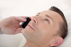 Happy man talking on mobile phone while relaxing on bed. Close royalty free stock photos