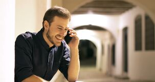 Happy man talking on phone sitting in the night stock footage