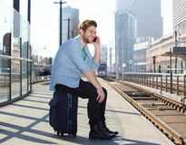 Happy man talking on mobile phone waiting for train Stock Photography