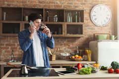 Happy man talking on phone and drinking wine in kitchen Stock Photo