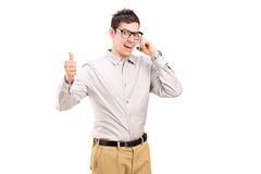 Happy man talking on phone and giving thumb up Royalty Free Stock Photo