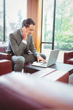 Happy man talking on the phone with his laptop. In the office Royalty Free Stock Image