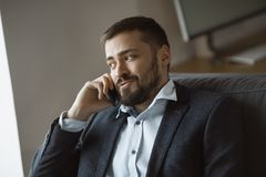 Happy Man in Talking on Smartphone. Cheerful businessman in suit talking on the phone, sitting on sofa in office. Portrait of a bearded concentrated man speaking royalty free stock image