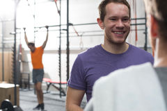 Happy man talking to male friend in crossfit gym Royalty Free Stock Images
