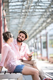 Happy man talking to woman while sitting on bench under shade Stock Photography