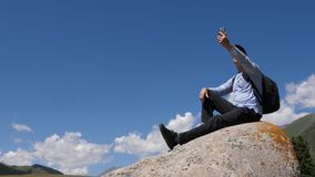 Happy man talking by video call by mobile phone sitting on big stone at hiking mountain