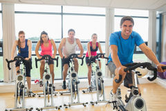 Happy man teaches spinning class to four people Royalty Free Stock Photography