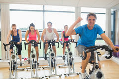 Happy man teaches spinning class to four people Royalty Free Stock Photo
