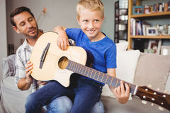 Happy man teaching guitar to son at home. Happy men teaching guitar to son while sitting on sofa at home stock photos