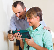 Happy man teaching son using electric drill Royalty Free Stock Photo