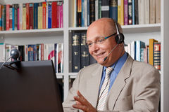 Happy man telephoning via internet. Happy and laughing man telephoning via the internet, online call, video-chat Royalty Free Stock Photography