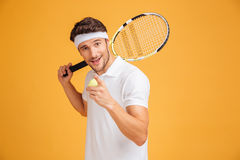 Happy man tennis player holding racket and pointing on you. Happy attractive young man tennis player holding racket and pointing on you over yellow background Royalty Free Stock Photo