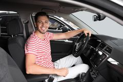Happy man testing new car. In salon royalty free stock images