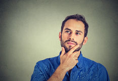 Happy man thinking daydreaming looking up isolated on gray wall background. Happy young man thinking daydreaming looking up isolated on gray wall background Royalty Free Stock Photos