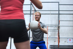 Happy man throwing medicine ball towards woman in crossfit gym Royalty Free Stock Photos