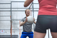 Happy man throwing medicine ball towards woman in crossfit gym Royalty Free Stock Photo