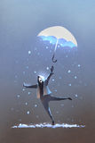 Happy man throws up a fantasy umbrella with falling snow Stock Photo