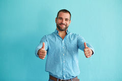 Happy man with thumbs up. On a turquoise background Royalty Free Stock Image