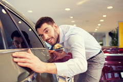 Happy man touching car in auto show or salon Stock Photos