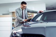 Happy man touching car in auto show or salon. Young Happy man touching car in auto show or salon stock photography