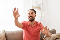 Happy man touching something imaginary at home Stock Image