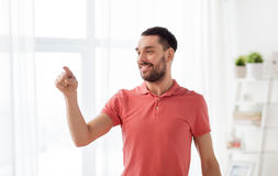Happy man touching something imaginary at home Stock Photos