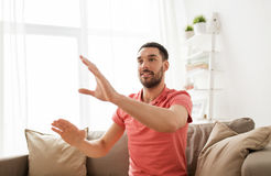 Happy man touching something imaginary at home Royalty Free Stock Image