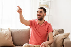Happy man touching something imaginary at home Stock Photo