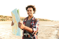 Happy man tourist with backpack standing and holding map outdoor Royalty Free Stock Images