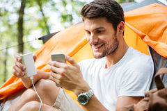 Happy man tourist charging battery of mobile phone in forest Royalty Free Stock Photography
