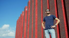 Happy man tourist stands on city street in sunglasses near a modern brick building stock video footage