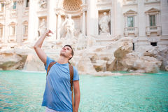 Happy man tourist trowing coins at Trevi Fountain, Rome, Italy for good luck. Caucasian guy making a wish to come back. Royalty Free Stock Photos