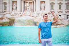 Happy man tourist trowing coins at Trevi Fountain, Rome, Italy for good luck. Caucasian guy making a wish to come back. Stock Photography