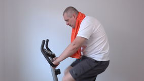 Happy man with a towel on exercise bike stock video