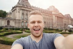 Happy man traveler with backpack taking selfie photo on central square Brussels, Belgium royalty free stock photography