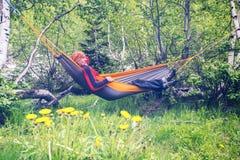 Happy man traveler is relaxing in hammock stock photos