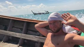 Happy Man Travelling in Traditional Thai Longtail Speedboat with T-Shirt Coiled on His Head. 4k UHD stock video footage