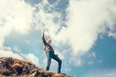 Happy man triumph his climb on the top of mountain Stock Photos