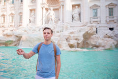 Happy man trowing coins at Trevi Fountain, Rome, Italy for good luck. Caucasian guy making a wish to come back. Royalty Free Stock Photos