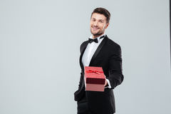 Happy man in tuxedo and bow tie giving present box Stock Photo