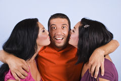 Happy man with two kissing women. Happy man making a surprised face while two brunette women kissing him,check also Friends Royalty Free Stock Image