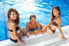 Happy man between two women at the swimming pool. Happy men between two beutiful women drinking cocktails at the swimming pool Stock Photo