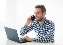 Happy man typing on laptop and speaking on mobile phone on white Royalty Free Stock Images