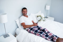 Happy man typing a text message on phone. In bedroom Stock Images