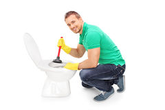 Happy man unclogging a toilet with plunger Royalty Free Stock Image