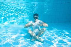 Happy man underwater showing OK sign and smiling, travel insurance royalty free stock photography