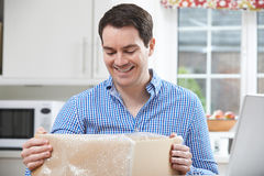 Happy Man Unpacking Online Purchase At Home. Man Unpacking Online Purchase At Home Royalty Free Stock Photography