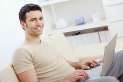 Happy man using computer. Happy young man in t-shirt sitting on sofa at home, working on laptop computer, smiling royalty free stock image